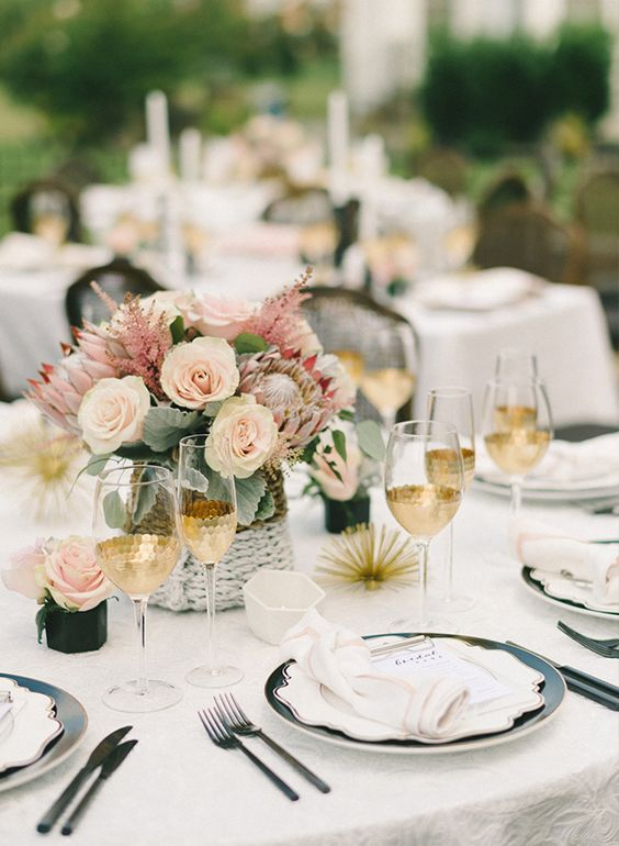 a modern and chic bridal shower tablescape with pink and blush blooms, pale leaves, gilded glasses, black plates and black cutlery