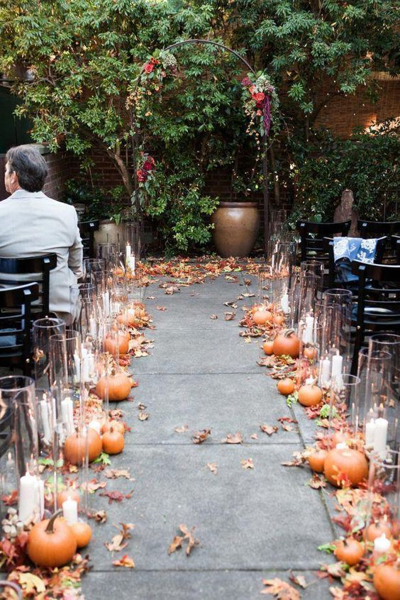 a pretty and simple boho fall wedding ceremony space wiht a delicate arch decorated with bold blooms, pumpkins, leaves and candles