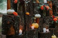 11 a cool backyard fall wedding space with a backdrop made of tree stumps, pumpkins, candles and bold blooms and greenery