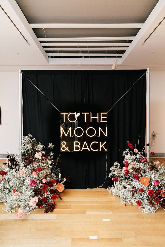 a fantastic modern wedding ceremony space wiht a black and neon backdrop, with baby's breath, pink, red, burgundy blooms