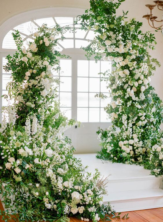 a fantastic overgrown flower wedding arch extended to ths stairs is a gorgeous idea for ane xtremely romantic wedding ceremony