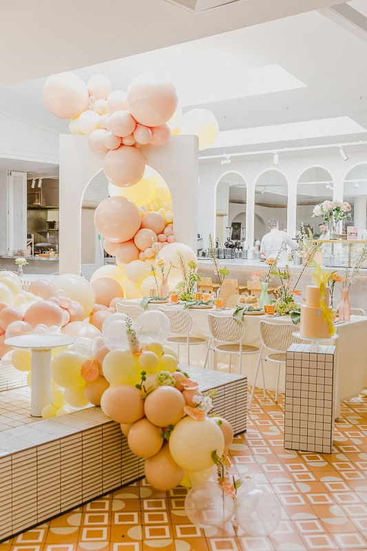 a modern bridal shower space decorated with pastel blooms, with lovely blooms and greenery and pastel decor is wow