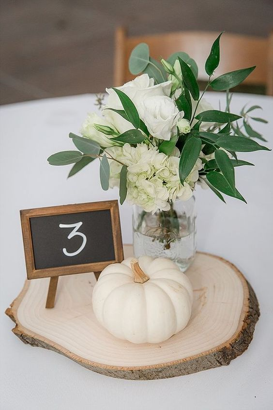 a pretty and elegant rustic fall wedding centerpiece of a wood slice, a pumpkin, white roses and hydrangeas and greenery and a chalkboard number