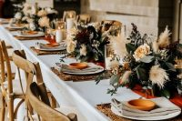 12 a beautiful fall wedding table setting with woven placemats, neutral linens, pastel blooms, greenery and pampas grass plus candles