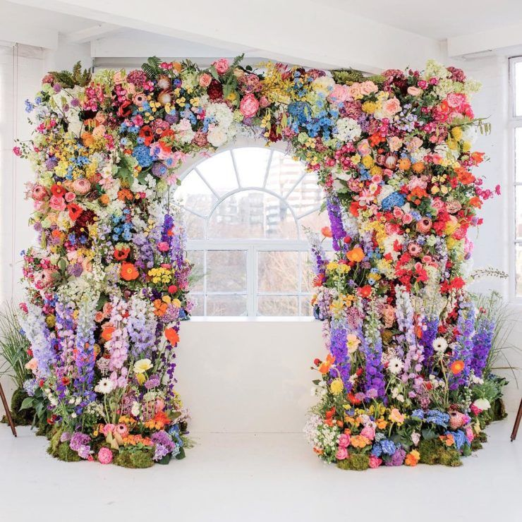 a fantastic colorful wedding arch with overgrown blooms in purple, pink, yellow, rust, orange, blue and white flowers and greenery