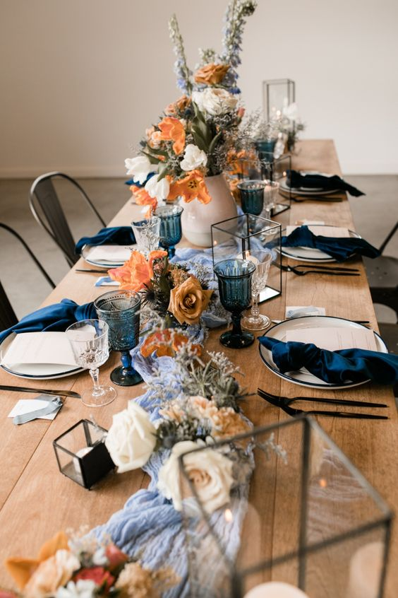 a lovely modern chic wedding tablescape with a blue runner, navy napkins and glasses, neutral and rust blooms and greenery, geometric candle lanterns