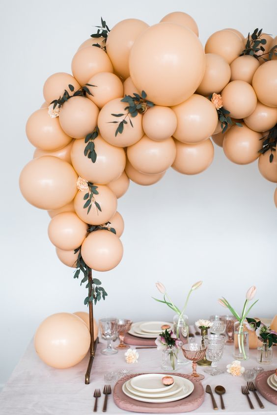 a modern bridal shower table done in pastel peachy shades and dusty pink ones, with balloons, tulips, stone chargers is amazing