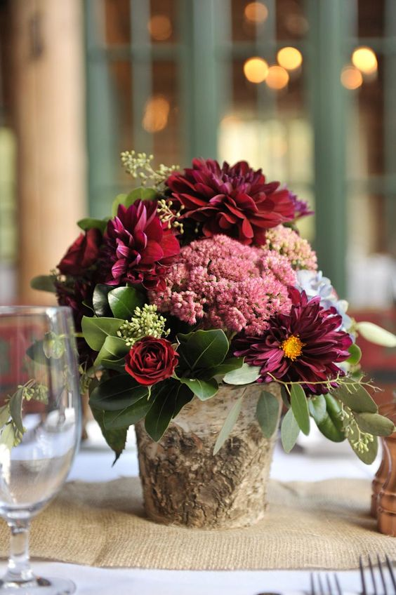 a simple and cute rustic fall wedding centerpiece of a tree stump, burgundy blooms of various kinds and greenery is a lush and beautiful idea