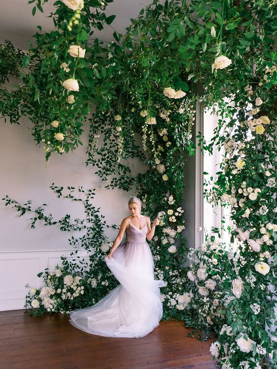 a fantastic overgrown flower wedding backdrop of lots of roses, peonies and greenery is a dreamy idea for a spring or summer wedding