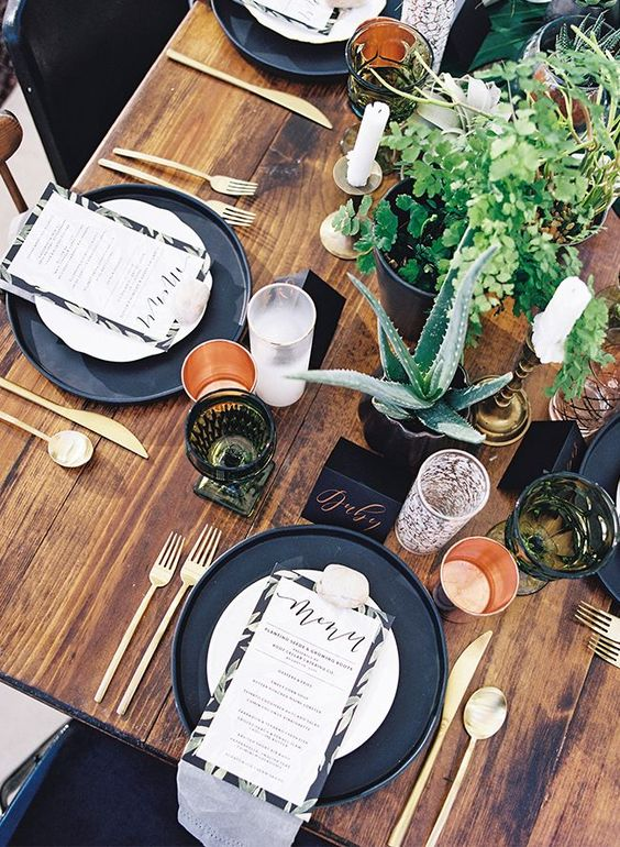 a lovely modern fall wedding tablescape with black chargers, potted greenery and succulents, gold cutlery, candles and colored glasses