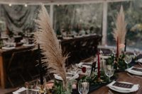 14 a beautiful moody fall wedding tablescape with a black runner and greenery, pampas grass and black and burgundy candles, gold touches and dark menus