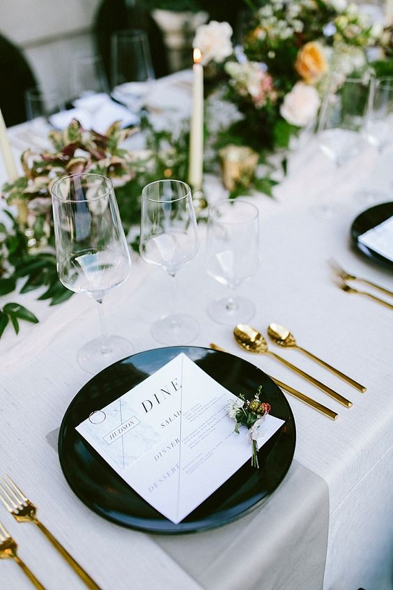 a modern elegant wedding tablescape with white linens, black plates, gold cutlery, a greenery runner with candles and neutral blooms