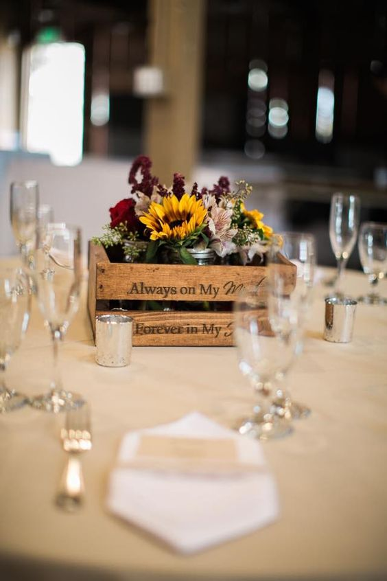 a rustic fall wedding centerpiece of a crate, sunflowers, burgundy and deep purple blooms, greenery and candles around