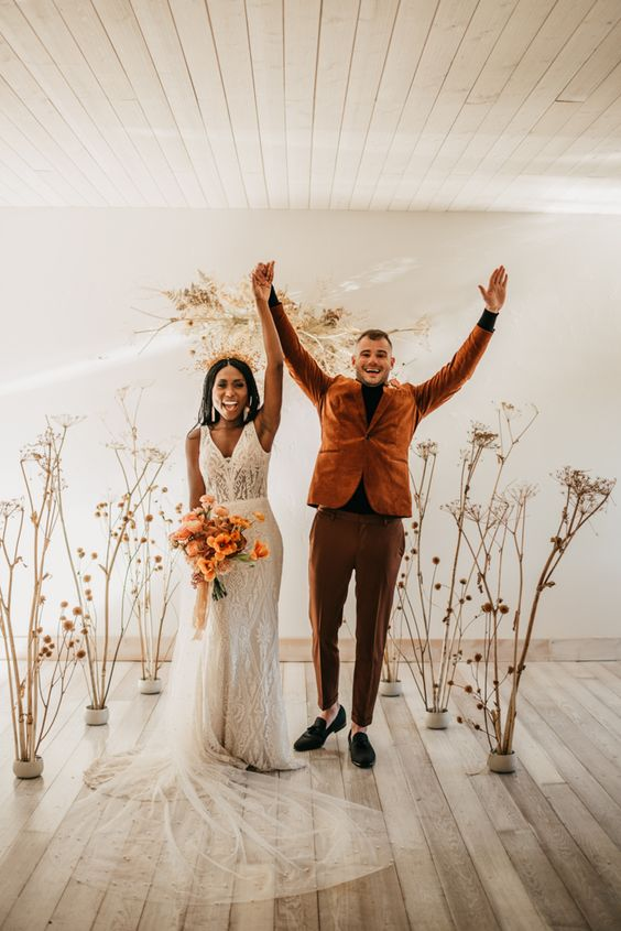 a modern fall wedding altar composed of dried branches and flowers plus some foliage on the wall is amazing