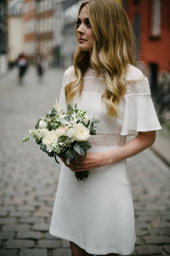 a pretty 70s inspired mini wedding dress of plain fabric, with beaded sheer inserts, a high neckline is a lovely idea to try