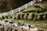 16 a chic backyard wedding reception table with neutral linens, green glasses, eucalyptus and white blooms plus candles