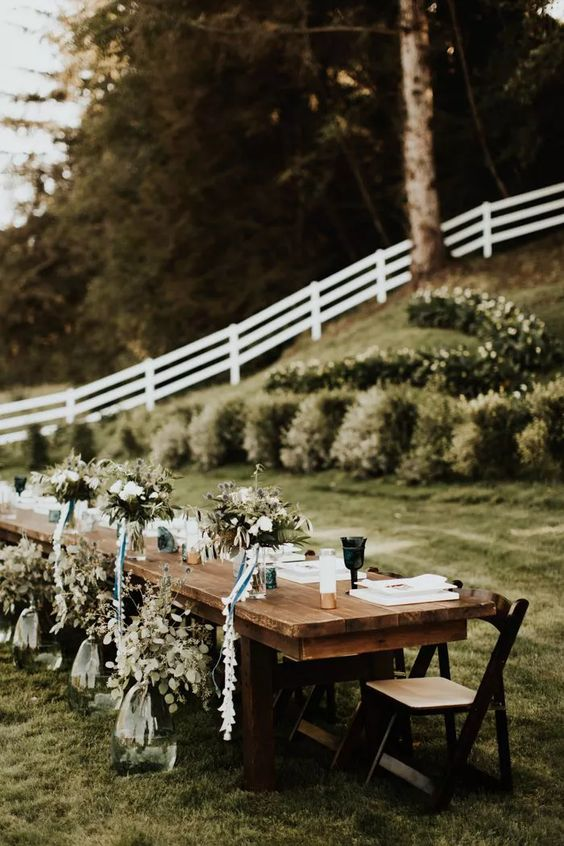 a chic backyard wedding reception table with neutral linens, green glasses, eucalyptus and white blooms plus candles