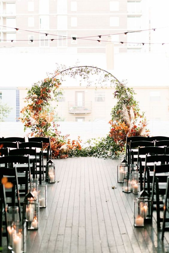 a modern fall wedding ceremony space with a round wedding arch decorated with greenery and bright fall leaves, with candle lanterns lining up the aisle