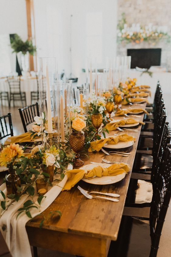 a beautiful and bright fall wedding tablescape with greenery, mustard-colored blooms and napkins, tall candles, brown glassses and greenery