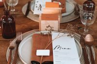 17 a chic terracotta fall wedding tablescape with an uncovered table, woven placemats, rust napkins, brown bottles with dried blooms