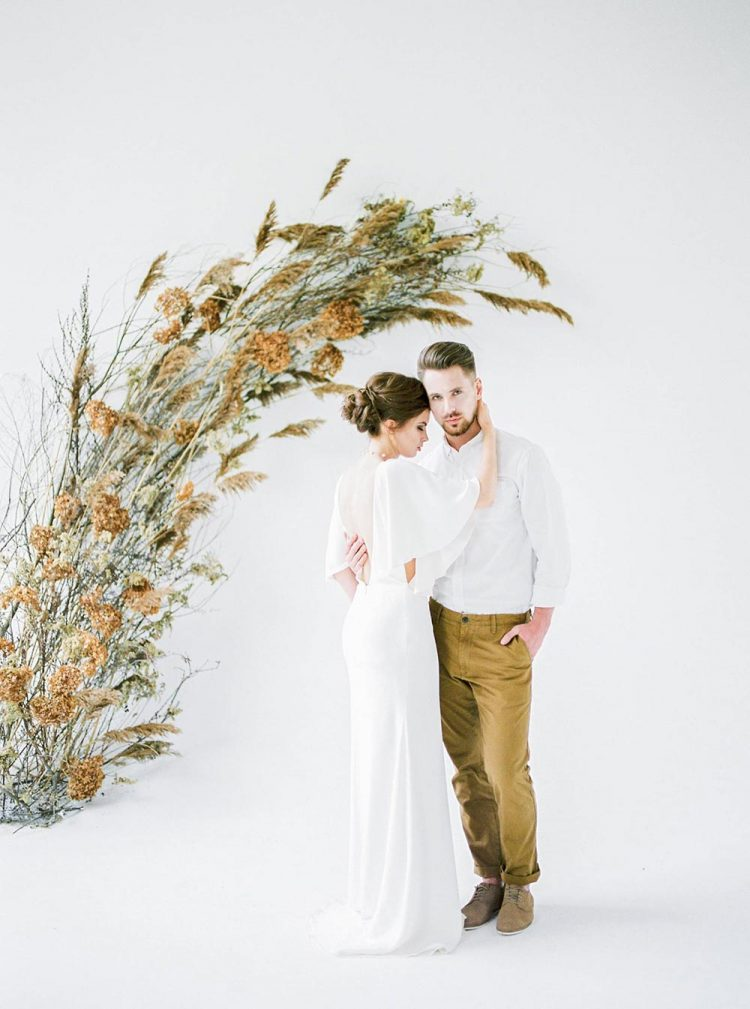 a modern boho wedding altar of overgrown blooms and grasses is a lovely idea if you want to make a statement and don't want many blooms