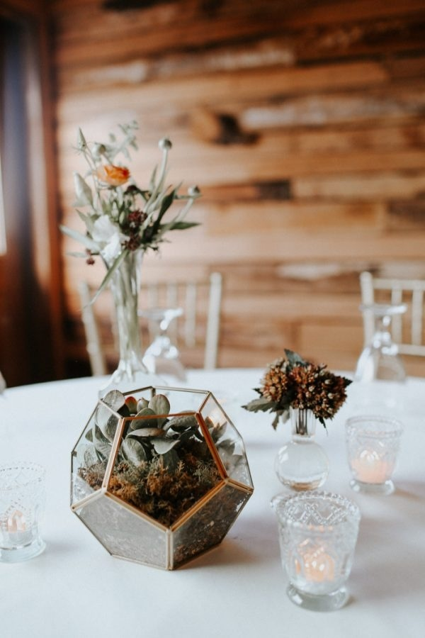 a modern fall wedding centerpiece of a terrarium with succulents, dried blooms and leaves, a rust flower and greenery in a vase