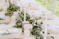 17 a neutral minimalist bridal shower tablescape with a eucalyptus runner, neutral porcelain and candles, copper cutlery and greenery touches