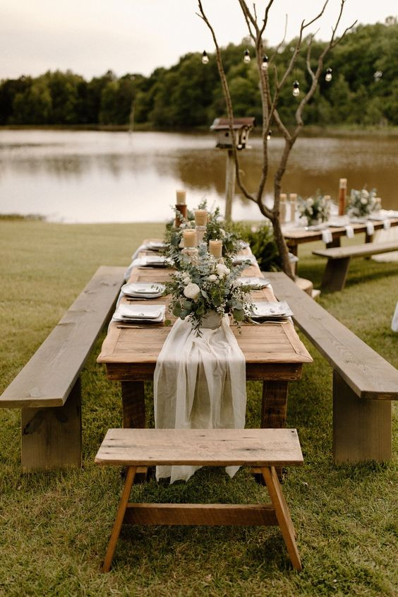 a delicate fall backyard wedding tablescape with candles, greenery and white blooms, white linens and string lights