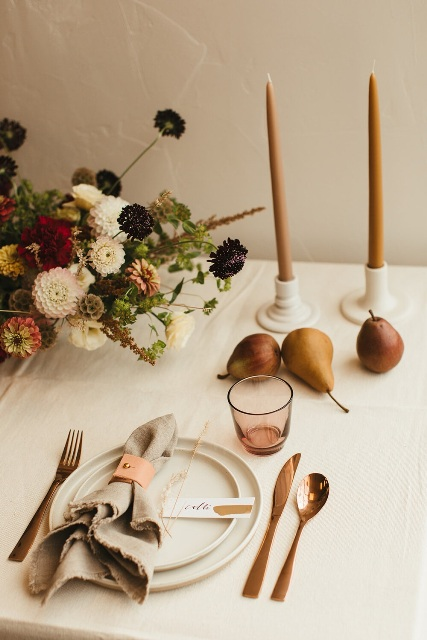 a modern fall wedding table setting with copper cutlery, muted color candles, neutral and bold blooms, a grey napkin,a  pink glass