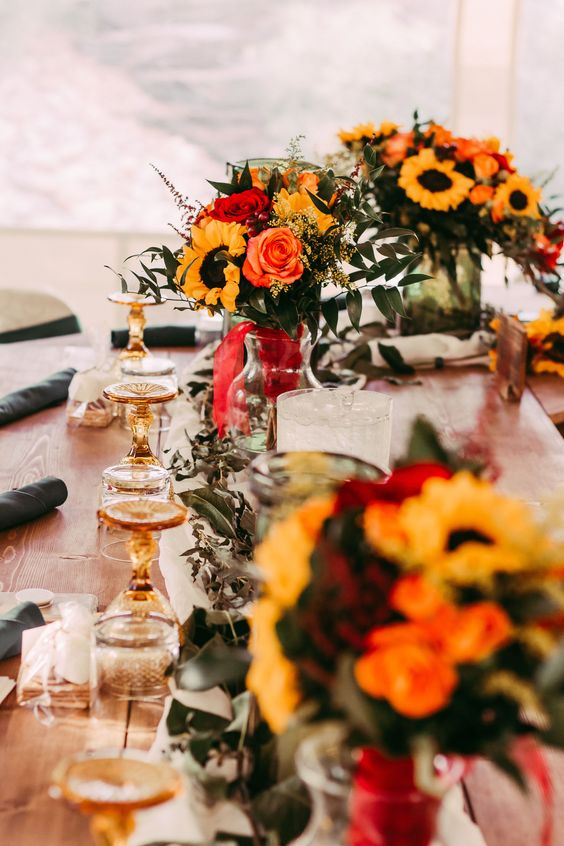 a bright fall wedding tablescape with amber glasses, sunflowers, red and pink roses and lots of eucalyptus is very chic and cozy