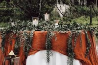 19 a fall backyard wedding tablescape with a white and orange tablecloth, lots of greenery, pillar candles and candle lanterns