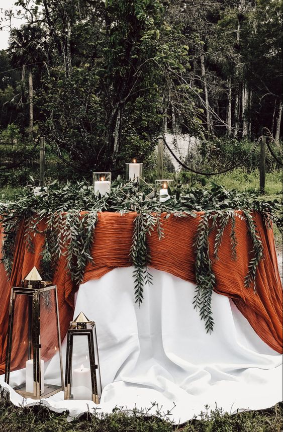 a fall backyard wedding tablescape with a white and orange tablecloth, lots of greenery, pillar candles and candle lanterns