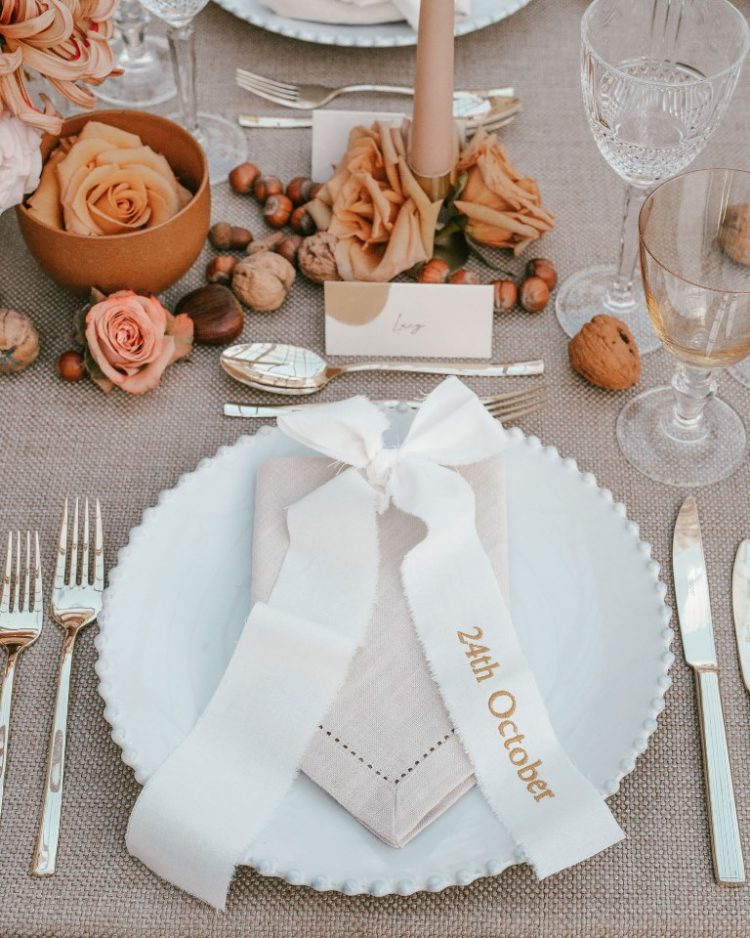 a modern fall wedding tablescape with neutral linens, nuts, pink and peachy roses, pink candles and elegant cutlery