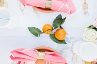 19 a modern tropical bridal shower tablescape with peachy chargers, pink napkins with gold rings, gold cutlery and citrus