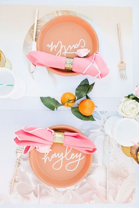 a modern tropical bridal shower tablescape with peachy chargers, pink napkins with gold rings, gold cutlery and citrus