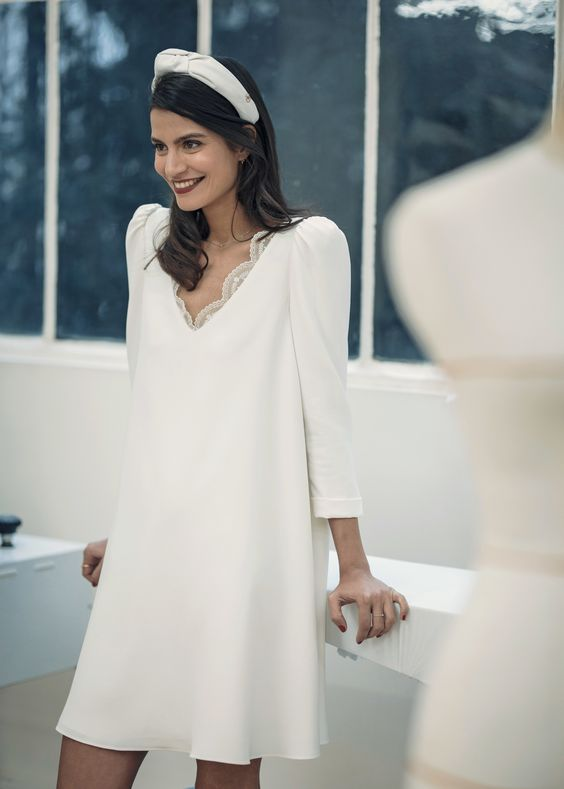 a pretty and casual mini wedding dress with an A-line silhouette, a V-neckline with lace, long sleeves and a cool headband as an accessory