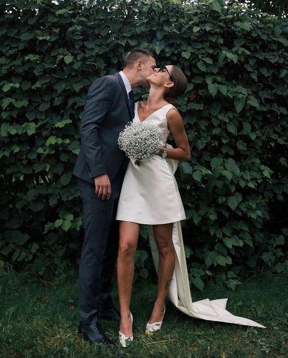 a plain mini wedding dress with thick straps, a V-neckline, white shoes, a sash with a large bow and super long straps instead of a dress train