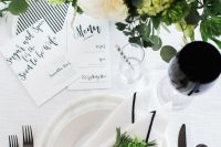 20 an elegant modern black and white bridal shower tablescape with neutral porcelain, black cutlery, black glasses, white and green blooms and striped stationery