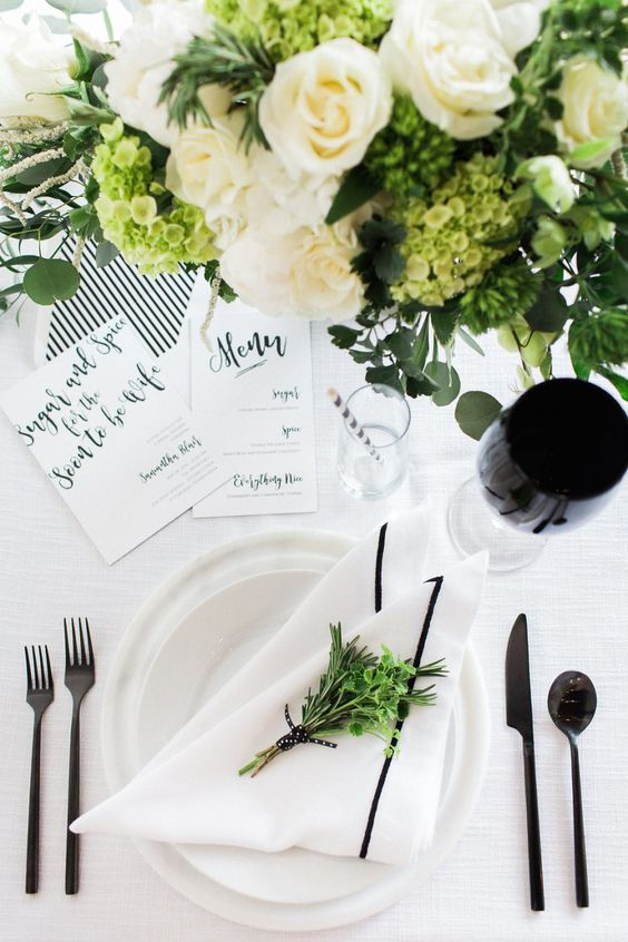 an elegant modern black and white bridal shower tablescape with neutral porcelain, black cutlery, black glasses, white and green blooms and striped stationery