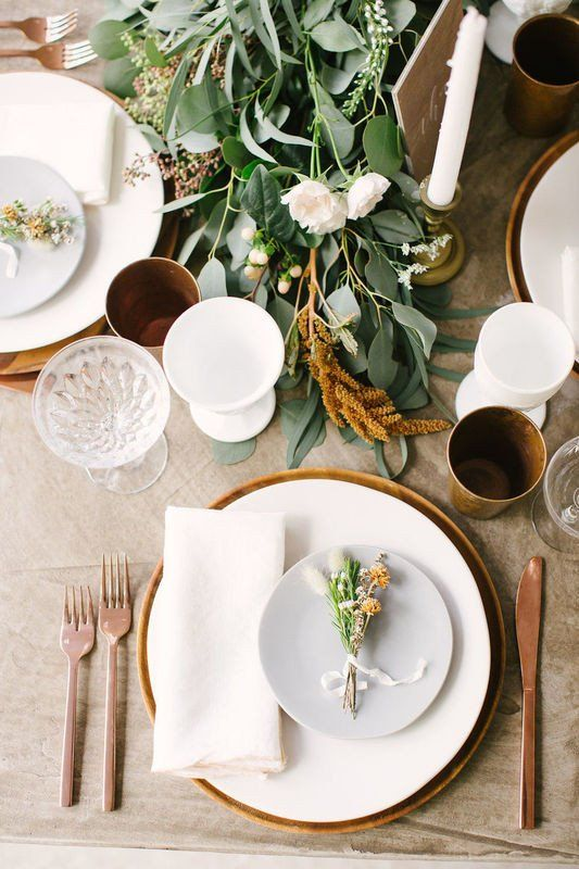 an elegant modern fall wedding tablescape with a greenery, rust and white bloom runner, white porcelain, wooden chargers and copper cutlery