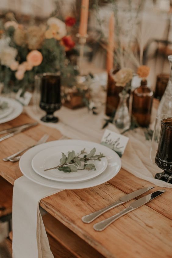 a chic rustic fall wedding tablescape with neutral linens, bold blooms and dried grasses, colorful candles and some greenery, dark goblets