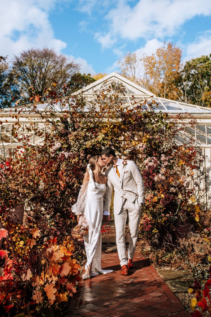a super lush and pretty modern fall wedding ceremony space done with lots of colorful leaves and greenery is wow