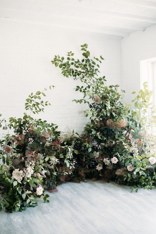 an overgrown flower wedding altar of greenery, colorful foliage, blush blooms looks like a piece of a real garden for a ceremony