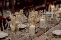 22 a stylish boho fall wedding tablescape with an uncovered table, dried blooms and grasses and candles plus neutral napkins