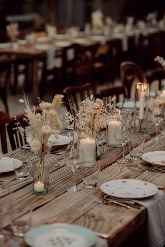 a stylish boho fall wedding tablescape with an uncovered table, dried blooms and grasses and candles plus neutral napkins