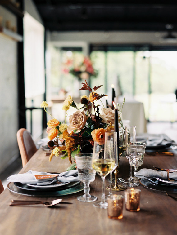 a super elegant modern fall wedding tablescape with hammered chargers, glasses, black candles, bright blooms and dark foliage