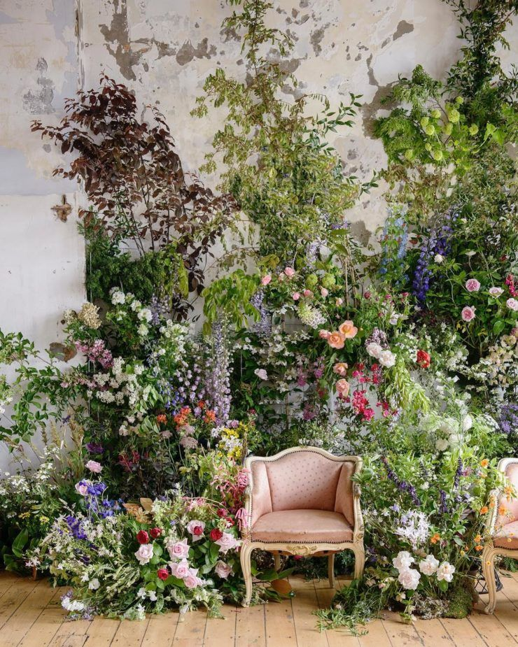 an overgrown flower wedding backdrop with lots of greenery, tons of pastel and bright blooms, greenery and dark foliage