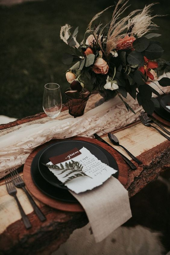 a moody rustic fall wedding tablescape with a wooden charger, a burlap napkin, blooms and greenery and black plates