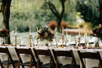 23 a refined backyard wedding tablescape with tall candles, gold touches and lovely burgundy and blush blooms and greenery