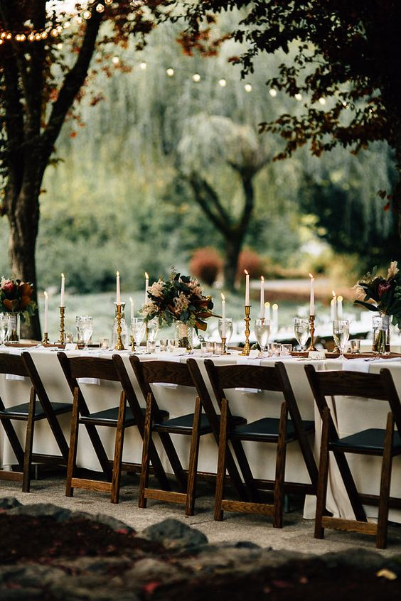 a refined backyard wedding tablescape with tall candles, gold touches and lovely burgundy and blush blooms and greenery